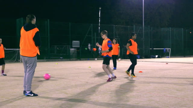A girls football team practise passing during training.