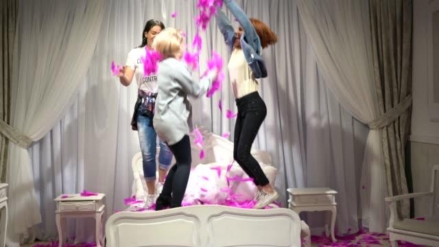 vídeos y material grabado en eventos de stock de amigos chicas teniendo diversión y baile en la cama - tres personas