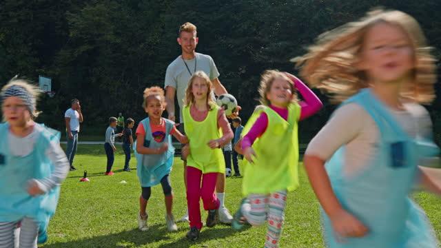 stockvideo's en b-roll-footage met meisjes van weinig voetballiga die hoge vijf met hun bus na de praktijk doen - sportteam