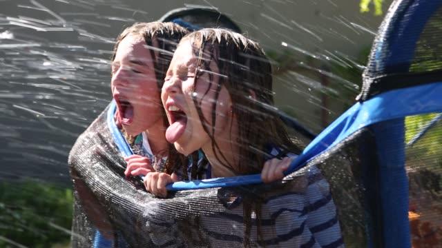 stockvideo's en b-roll-footage met girls getting splashed by hose - trampoline