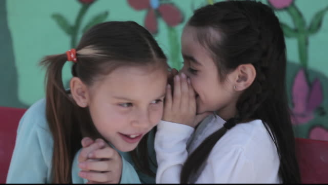 vídeos de stock, filmes e b-roll de cu girls giggling and whispering in each other's ears / los angeles, california, united states - formato letterbox