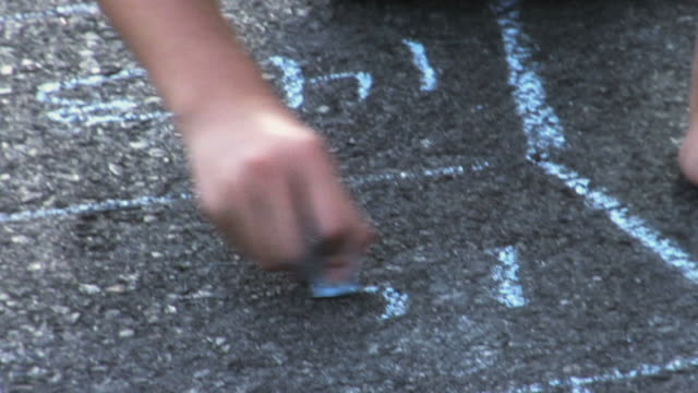 cu girls hand drawing hopscotch with blue chalk on sidewalk / langley, british columbia, canada.     - gessetto da lavagna video stock e b–roll
