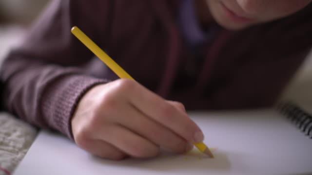 stockvideo's en b-roll-footage met cu pan girl's hand drawing on a piece of paper - alleen één tienermeisje