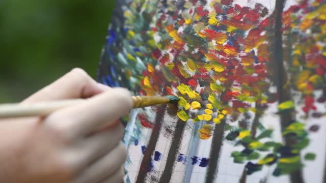 stockvideo's en b-roll-footage met meisje de hand schilderij - verfkwast