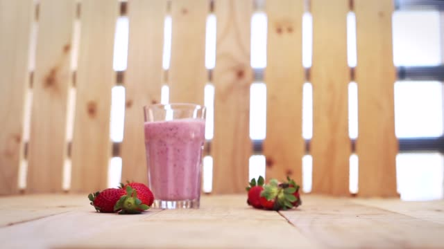a girl's hand putting a strawberry millshade on a table ourdoor. - strawberry milkshake stock videos & royalty-free footage