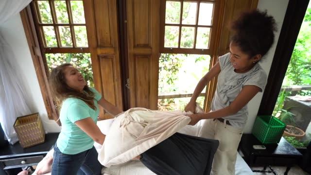 girls having a pillow fight - battaglia video stock e b–roll