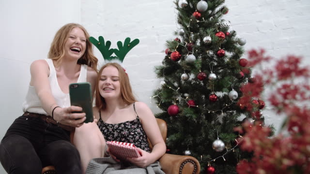 2 girls having fun with a reindeer antler diadem and taking selfies during christmas - antler stock videos & royalty-free footage