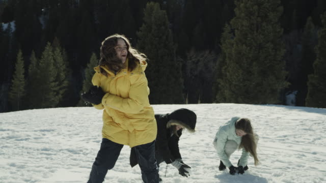 vidéos et rushes de girls having snowball fight in field / tibble fork, utah, united states - cadrage aux genoux