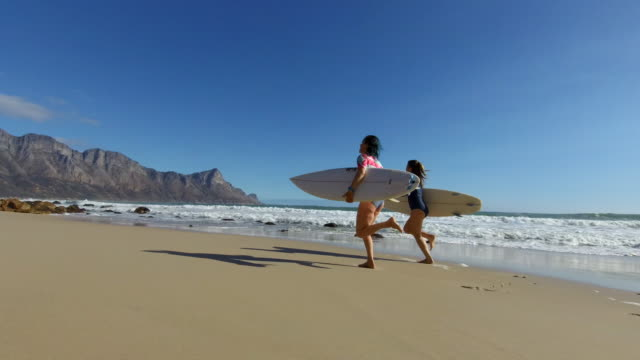 girls head out to go and surf - cape town stock videos & royalty-free footage