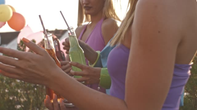 Girls holding drinking bottles on rooftop party