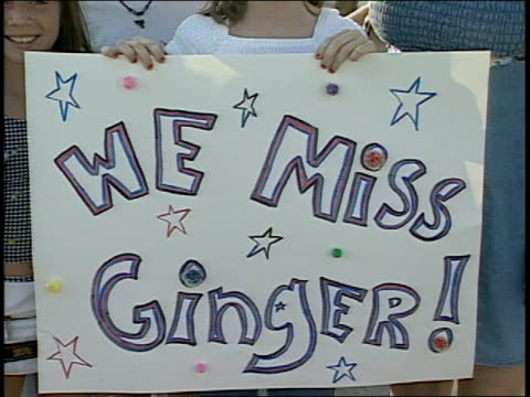 girls holding up 'we miss ginger' sign - 1998 stock-videos und b-roll-filmmaterial