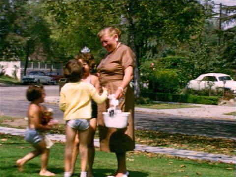 1953/54 home movie 3 girls hugging their grandma + running off - ワンピース型の水着点の映像素材/bロール