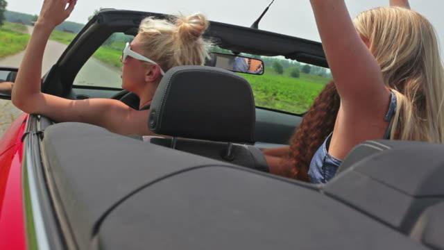 stockvideo's en b-roll-footage met hd: girls in convertible car - haar naar achteren