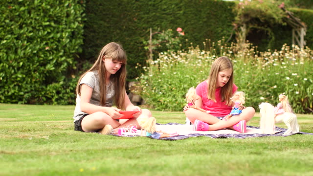 girls in garden playing with dolls & ipad - doll stock videos and b-roll footage