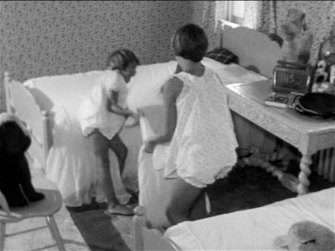 B/W 1957 2 girls in pajamas having pillow fight in bedroom / educational