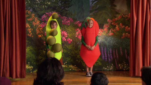 Girls in pea pod and carrot costumes bowing before audience at end of school play / boy in hot dog costume running onto stage / mother standing up and taking pictures / children taking bows / Los Angeles, California