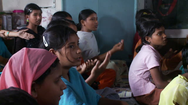 Girls in school sitting on mats singing and using hand gestures