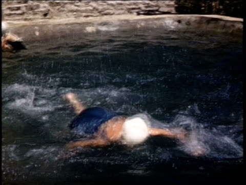 vídeos y material grabado en eventos de stock de girls in swimming pool play and swim with their father girls in swimming pool on july 01 1941 in california - gorro de baño