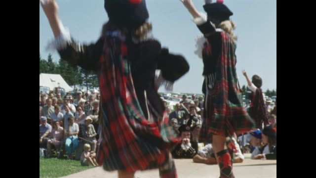 girls in traditional scottish dress perform highland dance on stage. - scottish culture stock-videos und b-roll-filmmaterial