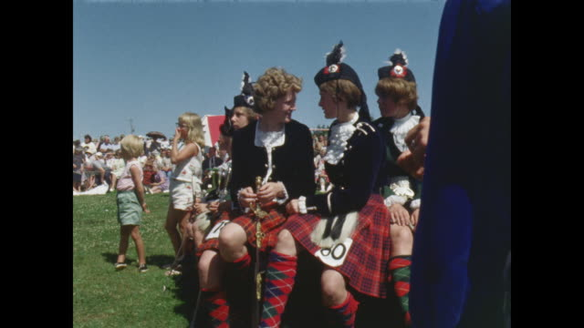 girls in traditional scottish dress talk as they wait to dance, pan to girls performing highland dance on stage. - scottish culture stock videos & royalty-free footage