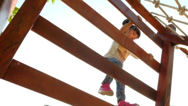 vídeos de stock, filmes e b-roll de meninas é escalada brinquedo no parque infantil - força