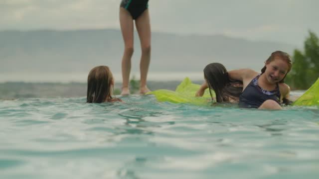 girls jumping and playing in swimming pool with pool raft / cedar hills, utah, united states - utebassäng bildbanksvideor och videomaterial från bakom kulisserna