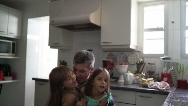 vídeos y material grabado en eventos de stock de chicas saltando en la cocina jugando con el padre en casa - genderblend