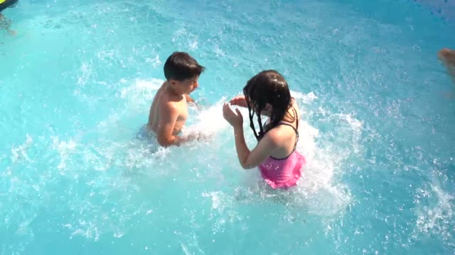 girls jumping together in the swimming pool in the garden of their friends - swimming shorts stock videos & royalty-free footage