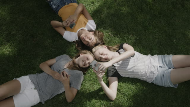 vídeos de stock e filmes b-roll de girls laying head to head on grass laughing at social media on cell phones / provo, utah, united states - com sombra