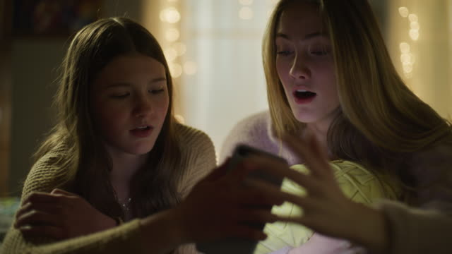 girls laying on bed at night seeing shocking social media on cell phone / cedar hills, utah, united states - x rated stock videos & royalty-free footage