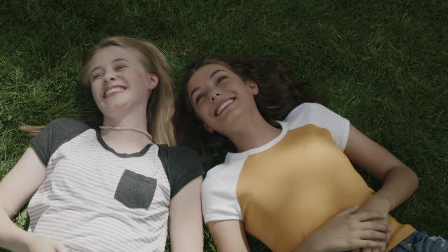 girls laying on grass and laughing / provo, utah, united states - brunt hår bildbanksvideor och videomaterial från bakom kulisserna