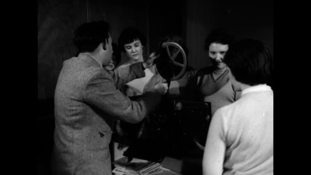 girls learn to use a film projector at a youth club; 1960 - proiettore cinematografico video stock e b–roll