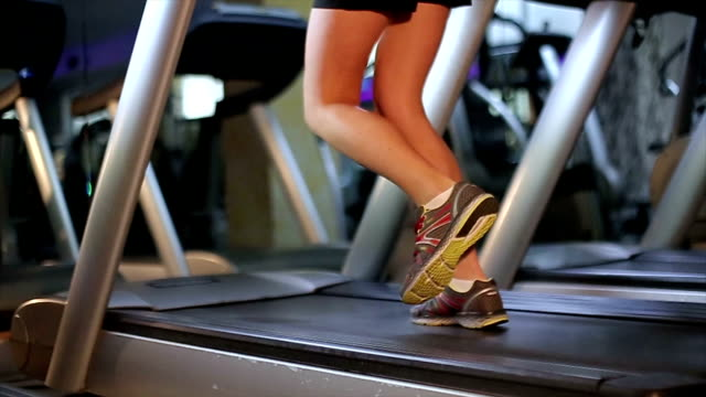 vídeos de stock e filmes b-roll de girls legs running on treadmill - decapitado