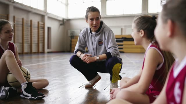mädchen hören ihren basketballtrainer beim training - mannschaftssport stock-videos und b-roll-filmmaterial