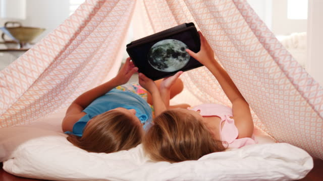 vídeos de stock e filmes b-roll de girls looking at digital tablet. - astronomia