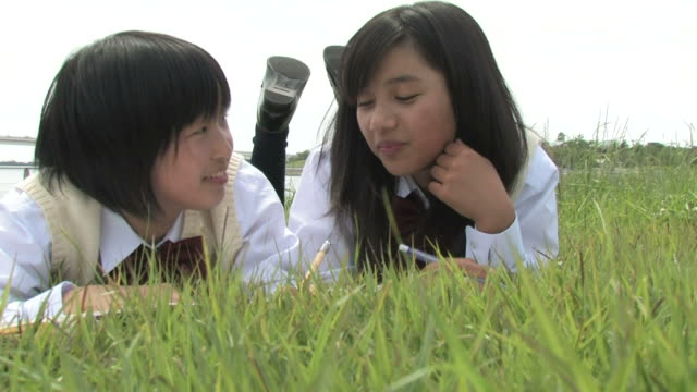 Girls lying on grass, writing in notebooks