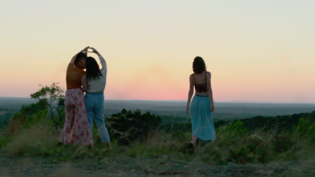 WS SLO MO. Girls make heart shape with hands and look out over valley from mountain clearing at magic hour.