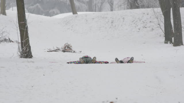 Girls making snow angels