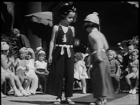 B/W 1936 2 girls modeling overalls in children's fashion show outdoors / Miami Florida / newsreel