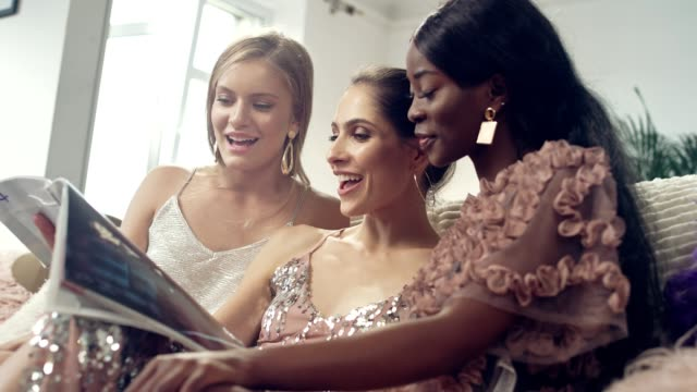 girls night fun. multi ethnic friends reading magazine - magazine stock videos & royalty-free footage