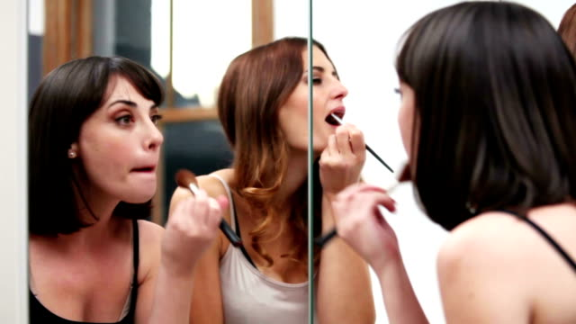girls night out  - friends apply makeup in a mirror - blusher make up stock videos and b-roll footage