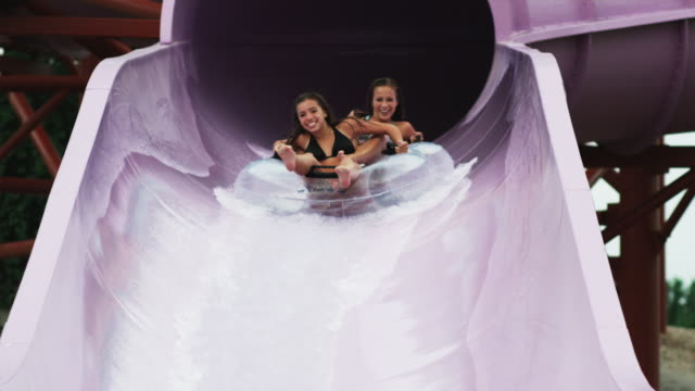 girls on a waterslide - 水泳用浮き輪点の映像素材/bロール
