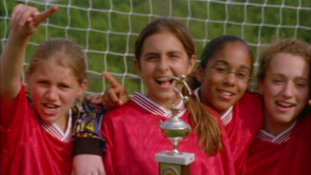 Girls on a youth soccer team celebrate after winning a trophy.