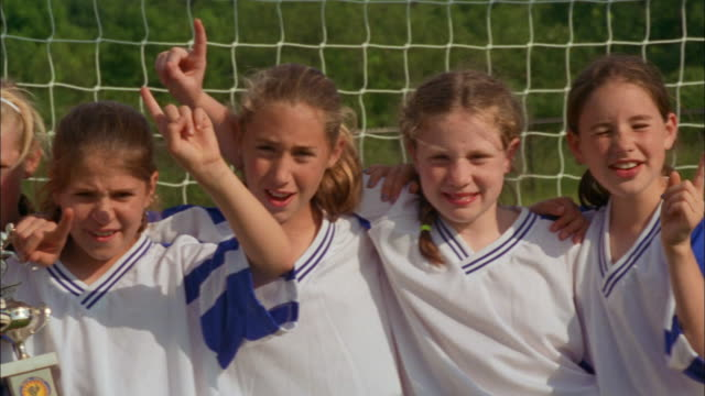 girls on a youth soccer team celebrate after winning a trophy. - football strip stock videos & royalty-free footage