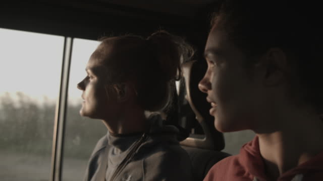 stockvideo's en b-roll-footage met girls on road trip looking out of window at sunset and listening to music - passagiersstoel