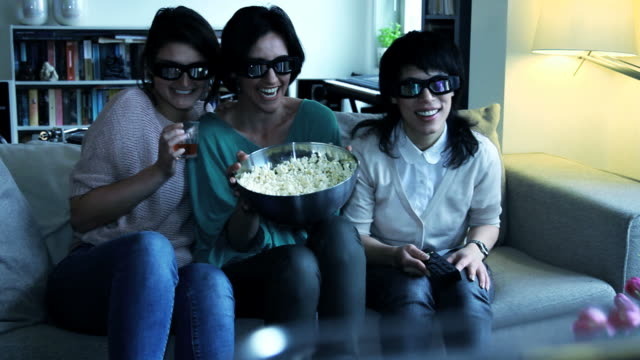 Girls on sofa watching Television with 3D glasses