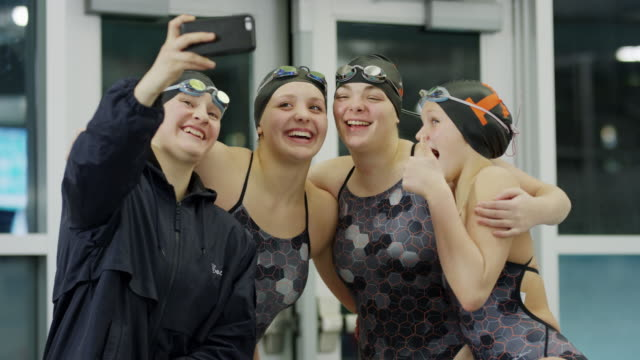 girls on swimming team posing for cell phone selfie / provo, utah, united states - provo点の映像素材/bロール