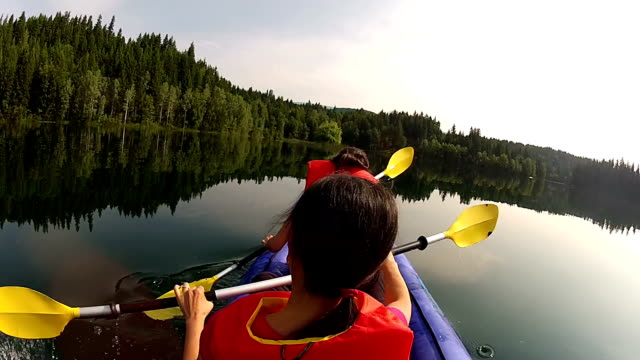 Girls paddling Kayak across a lake with pet dog