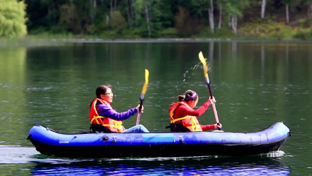 girls paddling kayak in lake - canoe stock videos & royalty-free footage