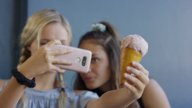 girls photographing ice cream cone with cell phone for social media / provo, utah, united states - provo stock-videos und b-roll-filmmaterial